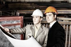 Experts at a plant. Industrial theme: two blue collars at a manufacturing area Royalty Free Stock Photography