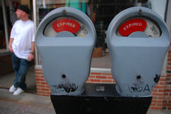 Expired Meter and Man. Parking meters expired, man haning out Stock Images