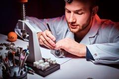Expirienced-Uhrmacher tut Stich für die Uhr der custmers an seiner Werkstatt lizenzfreie stockfotos