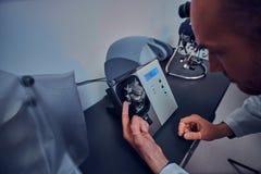 Expirienced-Uhrmacher tut Stich für die Uhr der custmers unter Verwendung des Spezialwerkzeugs an seiner Werkstatt lizenzfreie stockfotos