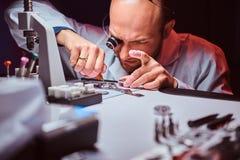 Expirienced-Uhrmacher tut Stich f?r die Uhr der custmers an seiner Werkstatt lizenzfreie stockfotografie