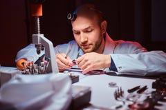 Expirienced-Uhrmacher tut Stich f?r die Uhr der custmers an seiner Werkstatt lizenzfreies stockbild
