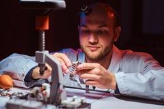 Expirienced-Uhrmacher tut Stich f?r die Uhr der custmers an seiner Werkstatt stockbild