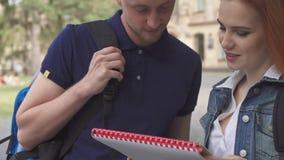 Explaines del estudiante masculino algo en cuaderno a su compañero de clase en campus almacen de video