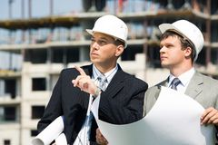 Explaining. Portrait of successful boss explaining and pointing to a place to foreman Royalty Free Stock Photo