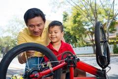 Explaining bike mechanism. Vietnamese men explaining mechanism of a bike to his son Royalty Free Stock Image