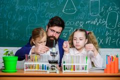 Explaining biology to children. How to interest children study. Fascinating biology lesson. Man bearded teacher work. With microscope and test tubes in biology stock images