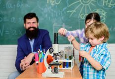 Explaining chemistry to kid. Fascinating chemical reaction. Teacher and pupils with test tubes in classroom. Interesting. School classes. School education stock image