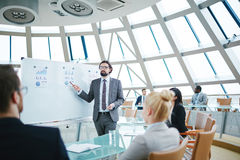 Explaining data to colleagues. Young businessman pointing at document on whiteboard during explanation stock photos