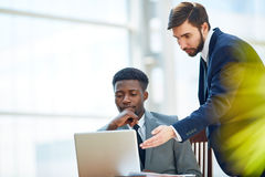 Explaining data. Two businessmen working online at meeting royalty free stock photography