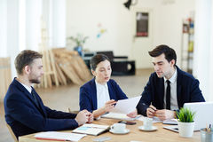 Explaining data. Young colleagues gathered by workplace for start-up meeting royalty free stock photo
