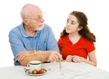 Explaining Democracy. Grandfather explains democracy to his teen granddaughter while filling out his absentee ballot. Isolated on white stock photo