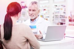 Positive senior pharmacist explaining an effect of prescription to a consumer. Explaining effect. Positive senior pharmacist explaining an effect of prescription royalty free stock photo
