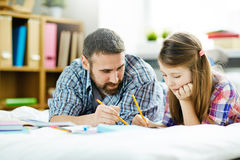 Explaining how to draw. Young men explaining his teenage daughter how to draw royalty free stock image