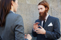 Explaining idea to subordinate. Young elegant managers having talk by wall of building Royalty Free Stock Image