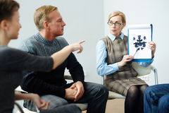 Explaining inkblot. Psychologist showing her patients Rorschach inkblot Stock Photos