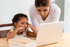 Explaining. Mother explaining her daughter something on the laptop Royalty Free Stock Photos