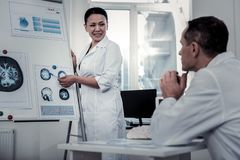Scientist explaining the processes in brain to her colleague stock photos