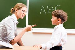 Explaining rules. Portrait of confident teacher explaining grammar to schoolchild who looking at her attentively Royalty Free Stock Images