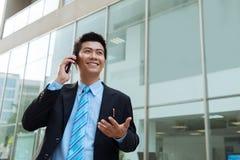 Explaining something on the phone. Smiling young manager explaining something on the phone royalty free stock photography