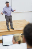 Explaining teacher standing in a lecture hall. Teacher talking and explaining things to the class which sitting in a lecture hall Royalty Free Stock Photography