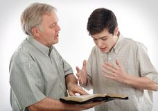 Explaining the Word of God. Father (or Preacher) explains God's Word to his son (or to a young man Stock Images