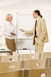 Explanation. Photo of successful businessman sharing ideas by whiteboard to pretty partner stock image