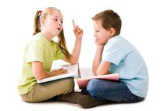 Explanation. Portrait of cute schoolgirl explaining something to pensive lad who listening to her attentively Royalty Free Stock Images