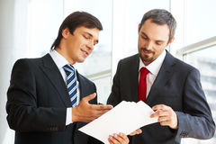 Explanation. Image of confident businessman looking at document in partner�s hand while discussing it royalty free stock photos