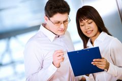 Explanation. Photo of handsome boss looking at notes in secretary�s hand stock photo