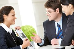 Explanation. Photo of smart woman holding paper in hand with her two colleagues looking at her with smiles stock photos