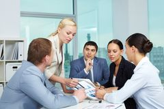 Explanation. Business people looking at paper with charts stock images