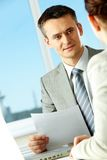 Explanation. Smart businessman explaining something to his colleague in office stock photo