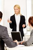 Explanation. A businesswoman standing at a whiteboard and speaking to her colleagues stock photos