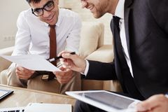 Explanation. Businessman pointing at document held by his colleague while explaining his viewpoint royalty free stock images