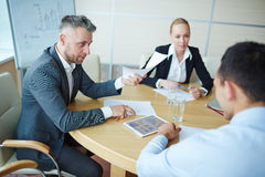 Explanation of data. Employer giving document with data to young manager royalty free stock photo