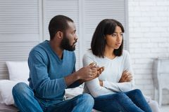 Kind calm man explaining the situation to his girlfriend. Explanation. Emotional young women looking offended while her boyfriend explaining her the situation royalty free stock photography