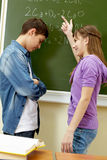 Explanation of formula. Clever girl pointing at blackboard while explaining formula to classmate royalty free stock images
