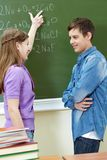 Explanation of formula. Clever girl pointing at blackboard while explaining formula to classmate royalty free stock photos