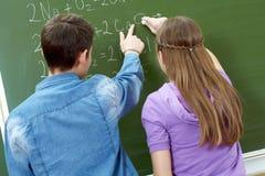 Explanation of formula. Back view of guy pointing at blackboard while explaining formula to girl stock photography