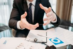 Explanation hand gesture business man holding. Explanation. hand gestures. business man holding in hands. business papers on the desk. office working space stock photos