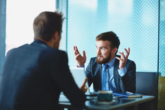 Explanation. Handsome employee explaining his point of view to colleague at meeting royalty free stock image