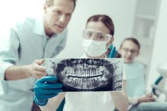Attentive dentist showing the X-ray to a patients father Stock Images