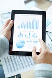 Explanation of statistics. Market analysis or economic statistics in touchpad during business presentation royalty free stock photo