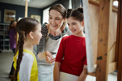 Explanation of teacher. Young women mentoring her little learners of painting course royalty free stock image