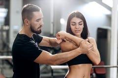 Explans тренера фитнеса к атлетической девушке одетой в черных одеждах спорта как работает мышцы оружий стоковое изображение