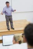 Explicando o professor que está em um salão de leitura Fotografia de Stock Royalty Free