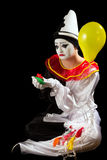 Exploded balloons. Crying pierrot clown holding exploded balloons in his hand Royalty Free Stock Photo