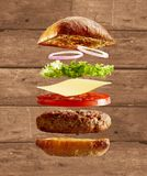 Exploded diagram of burger, buns and ingredients. An exploded diagram view of a burger, with onion, lettuce, cheese, tomato and a toasted bun on a rustic timber Royalty Free Stock Photos