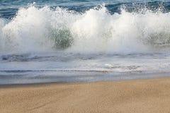 exploderande vågfärgstänk med att skumma backsplash på den sandiga stranden royaltyfria bilder